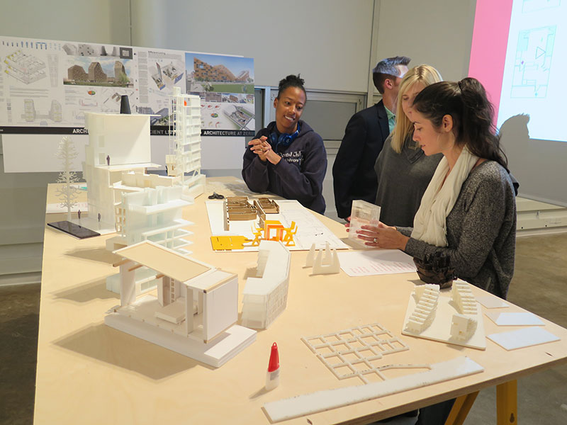 Architecture students lean on a table holding 3D-printed building models.