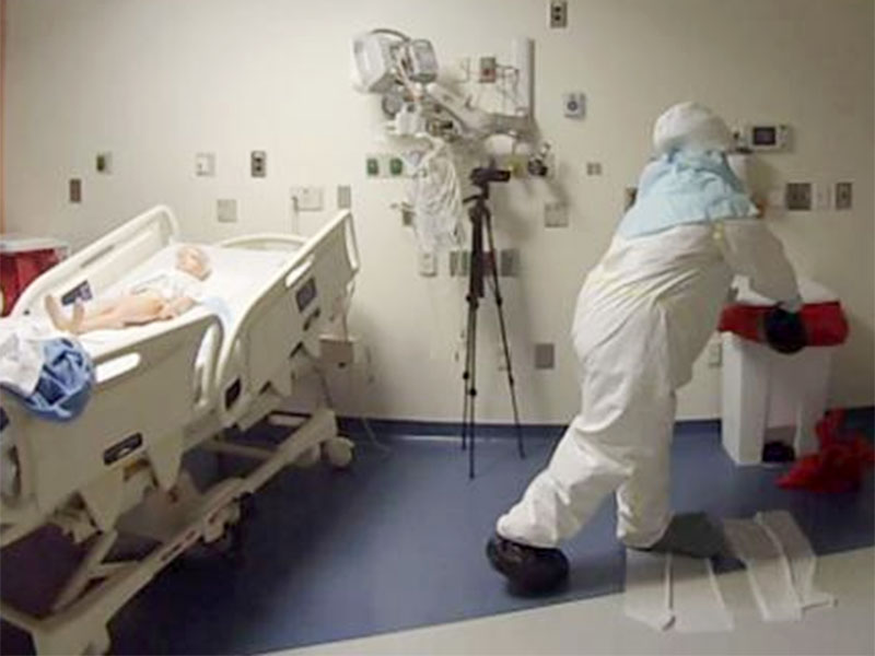 A children's hospital worker wears protective clothing in a quarantine room.