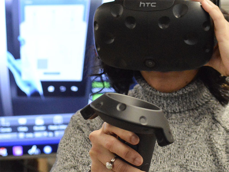 An undergraduate student wears a VR headset and uses a joystick.