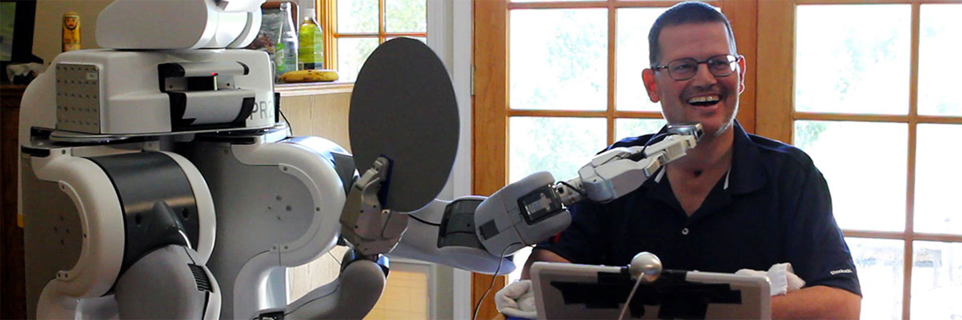 A quadriplegic man gets help shaving his face from a robot.