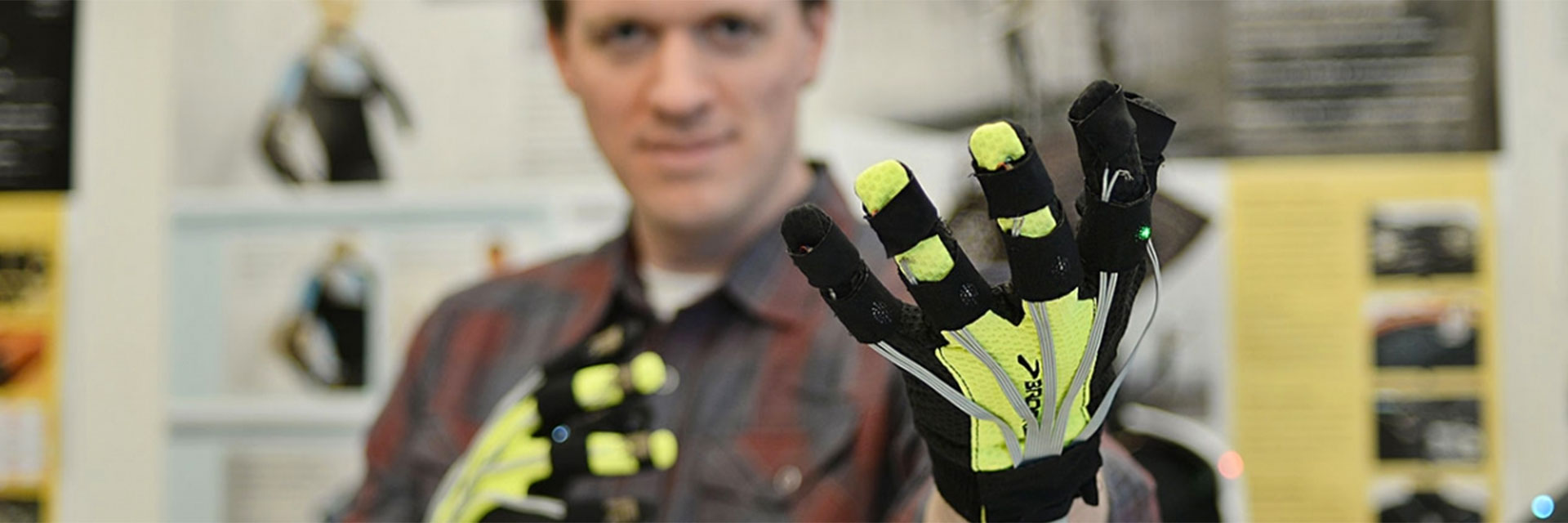 An industrial design student researching wearable technologies wears yellow and black haptic gloves.