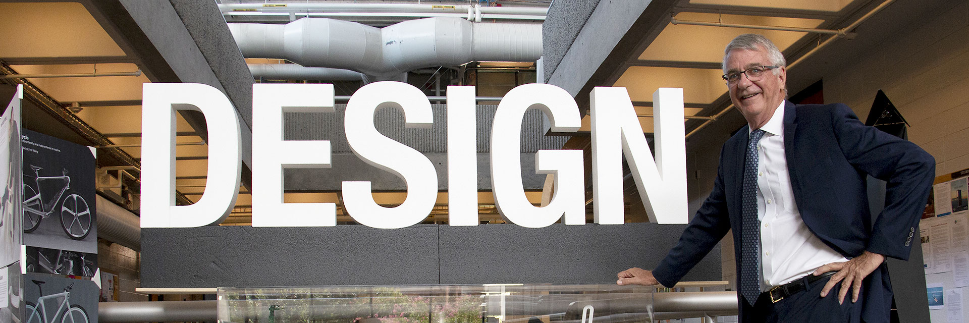 College of Design dean Steven French stands next to large foam letters that spell the word DESIGN.