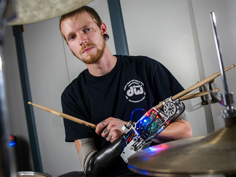 Photo of Jason Barnes behind a drum kit wearing a prosthetic drumming arm.