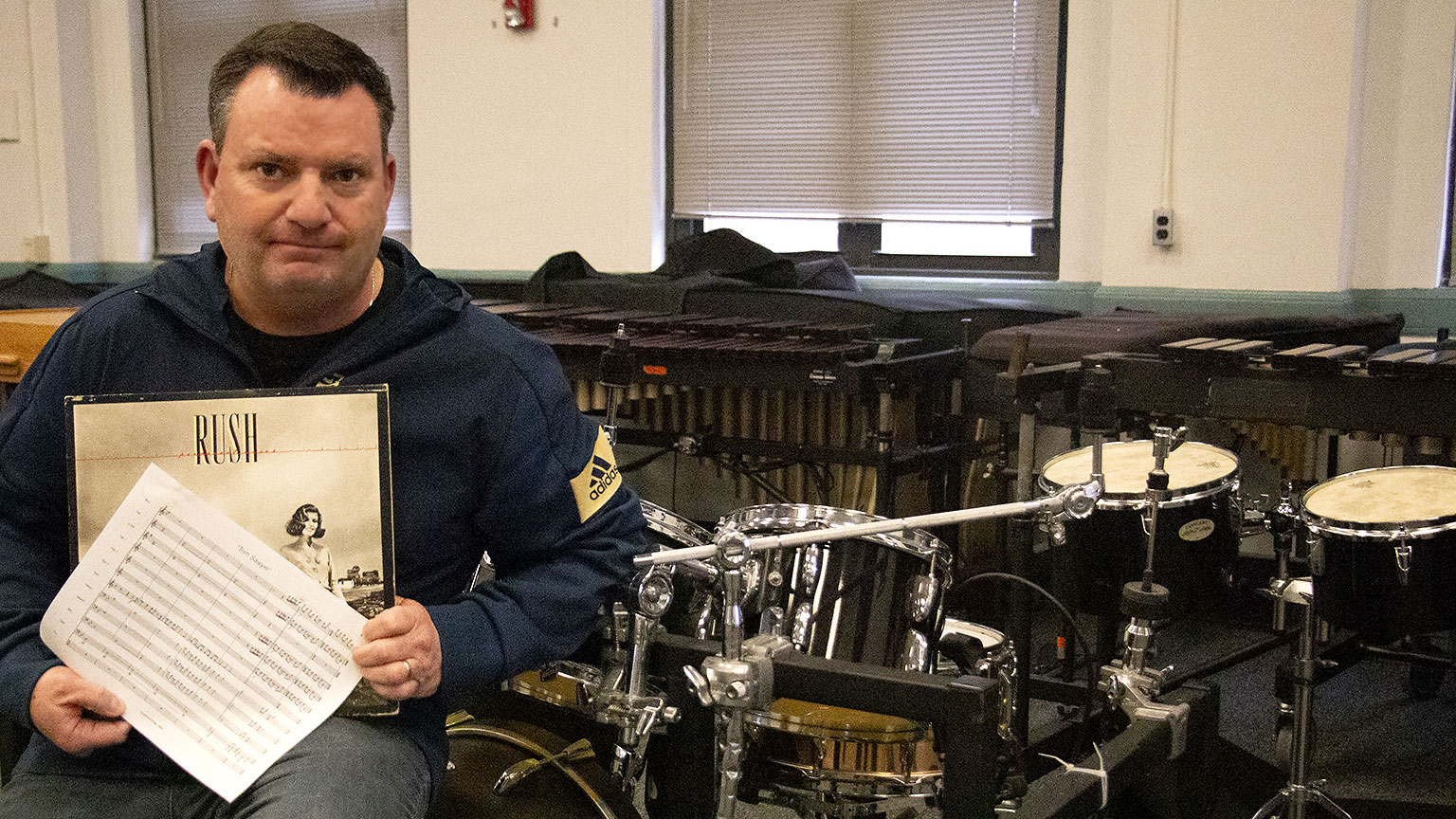 "Chris Moore sits in front of percussion instruments, holding the sheet music for ""Tom Sawyer"" and his vinyl copy of ""Permanent Waves."""