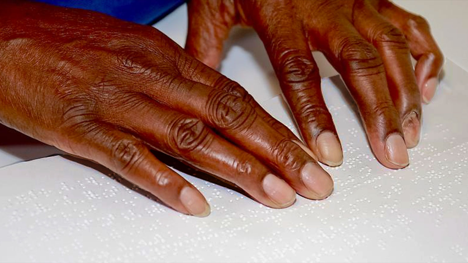A Black woman's hands are shown reading braille on a page.