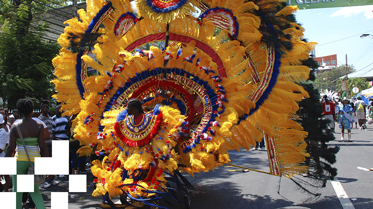 A Carnival dancer wears a gigantic  dancing sculpture, covered in yellow feathers.