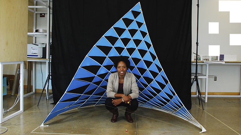 Vernelle Noel poses in front of a sail she designed and constructed using parameters from Carnival dancing sculptures.