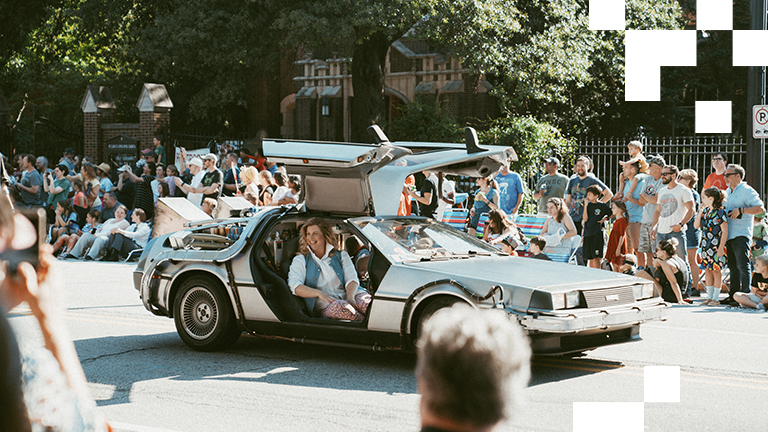 Crowds of onlookers watch a Dolorean and a 'Back to the Future' cosplayer during the Dragon Con parade.