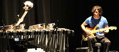 A graduate student from the School of Music plays guitar with a robot.