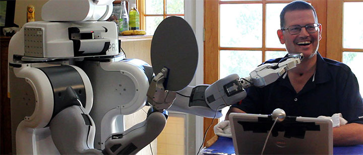 A robot shaves the face of a quadroplegic man.