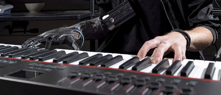 Amputee Jason Barnes plays piano with his natural arm and hand, and his other prosthetic arm and hand.