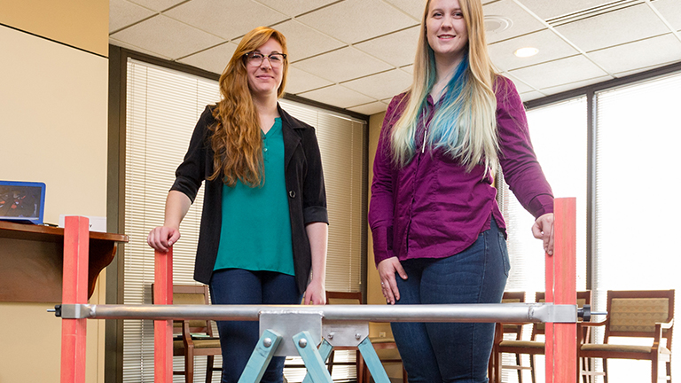 Two industrial design students stand in front of their collapsible parallel bars invention.